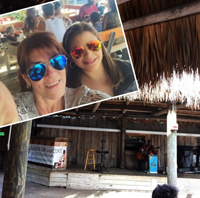 Mother and daughter enjoy live music performed in a beach cafe