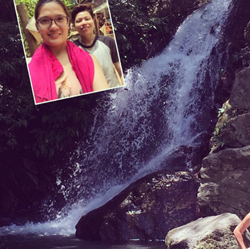 Attractive girl takes selfie near a waterfall while on tour