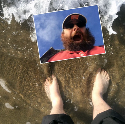 Man with a funny red beard steps into cold water of Pacific ocean for the first time in his life