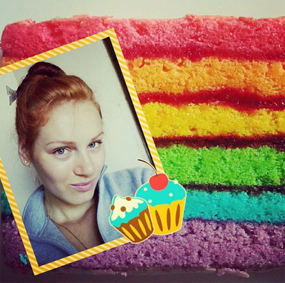 Red-head girl takes selfie with a freshly cooked rainbow cake