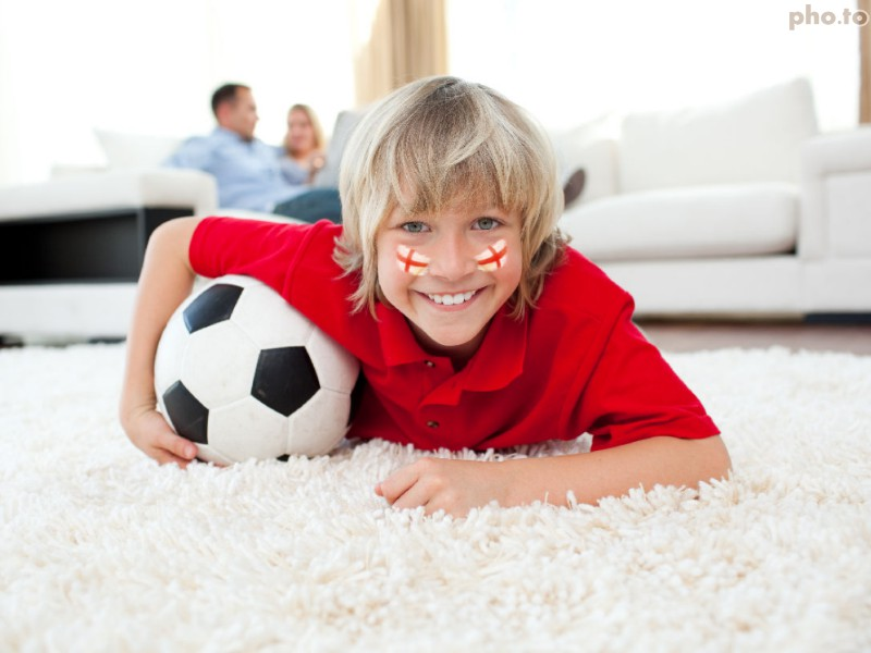 A little football fan with patriotic England flag face painting for FIFA World Cup 2014 watches TV excited