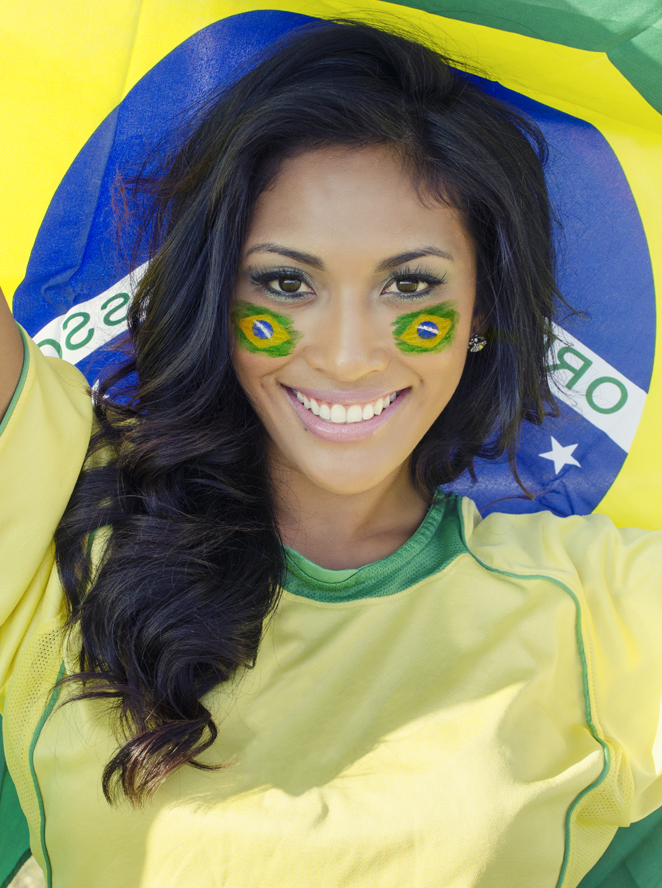 A charming football fan who support Brazil team at FIFA World Cup 2014 smiles