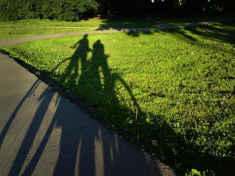 Shadow on grass of two people on cycles