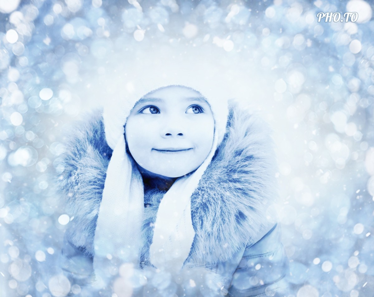 Glittering blue bokeh effect us applied to a winter photo with a little smiling girl