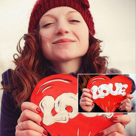 A girl holds big Valentine's card in her hands