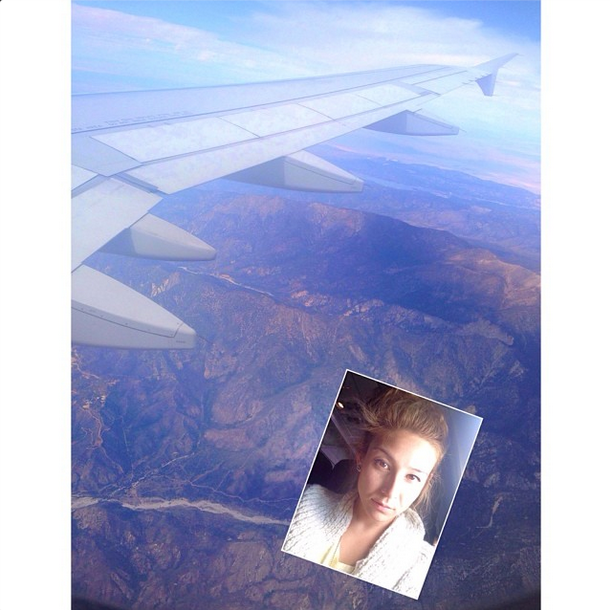 Beautiful blonde girl is taking selfie in a plane