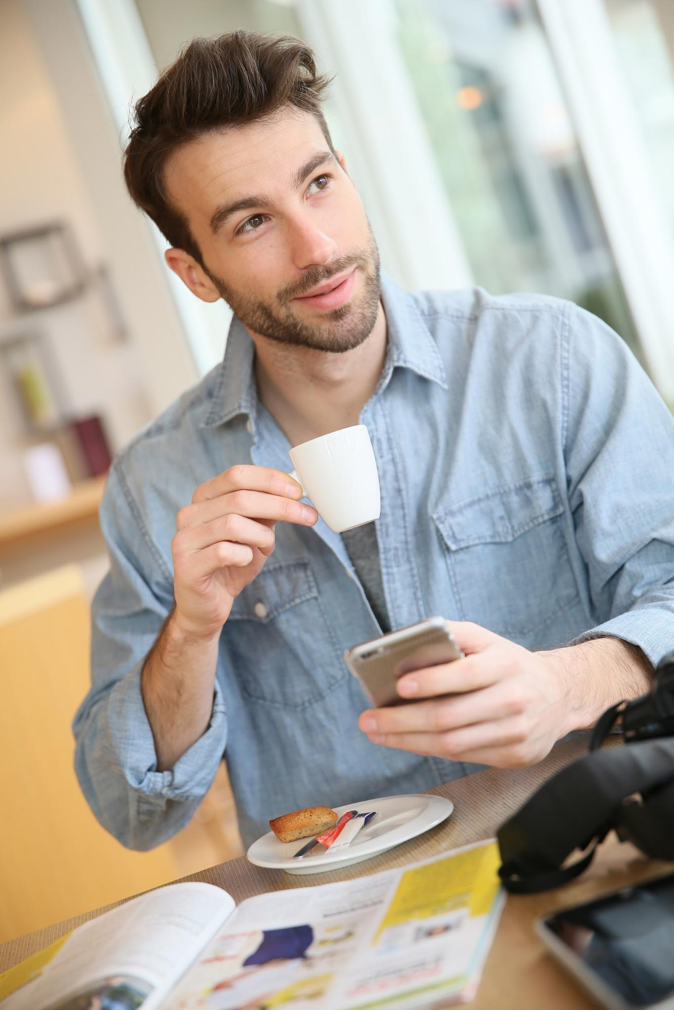An attractive guy drinking coffee in cafe in early morning
