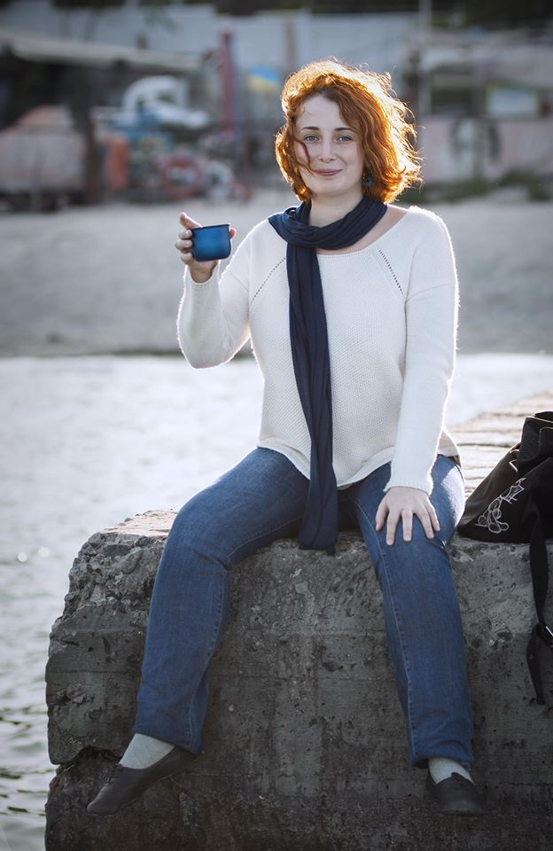 Redhead girl drinking cocoa from thermos on the pier near sea