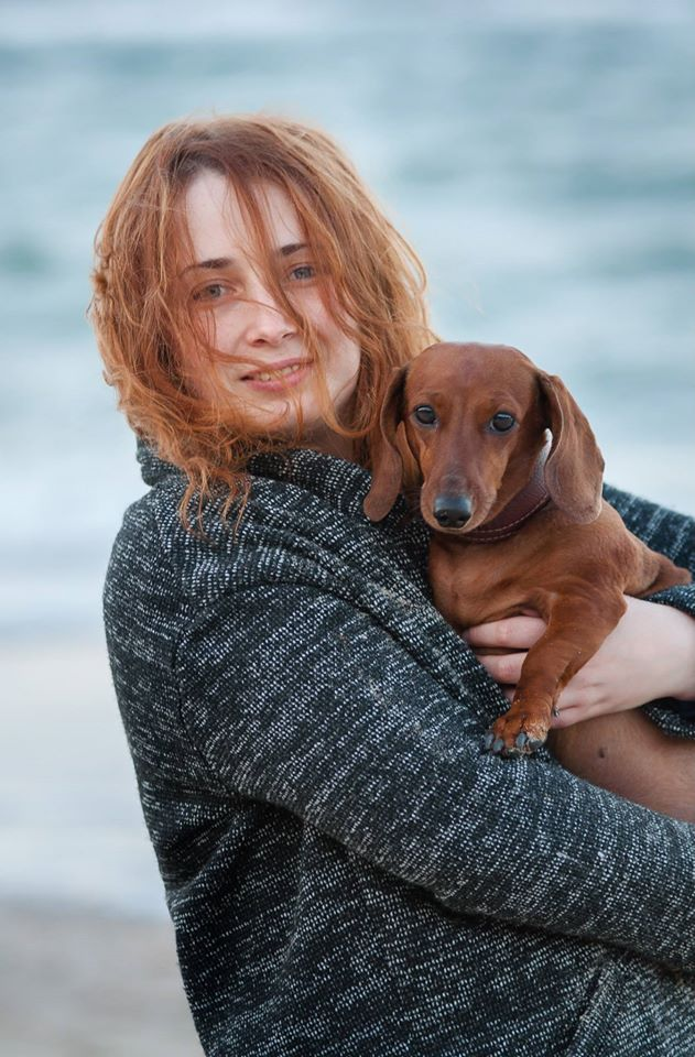 Girl with dachshund going out near autumn sea