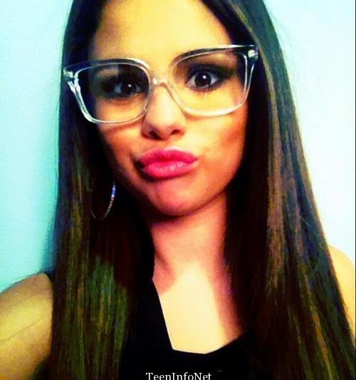 Selena Gomez is making a cute duck face with glasses