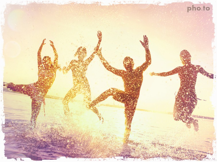A photo of 4 people dancing in water on a beach, edited with a color filter