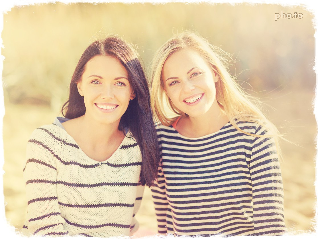 A portrait photo of two beautiful girls edited with a color filter to add warm and golden tints