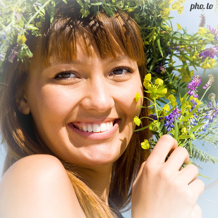 A portrait photo of a girl in flower wreath edited with mobile app to add a light white vignette