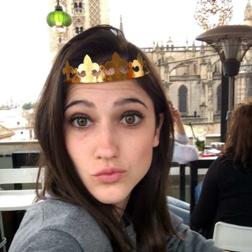 Photo of a young beautiful girl posing in a cafe decorated with a funny sticker crown
