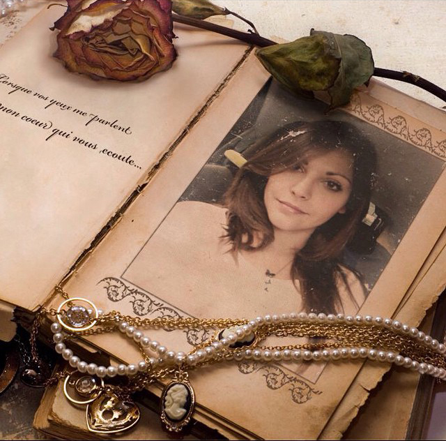 Photo of a young attractive girl put into a vintage photo frame with adornments: perl necklace, rose, paper, etc